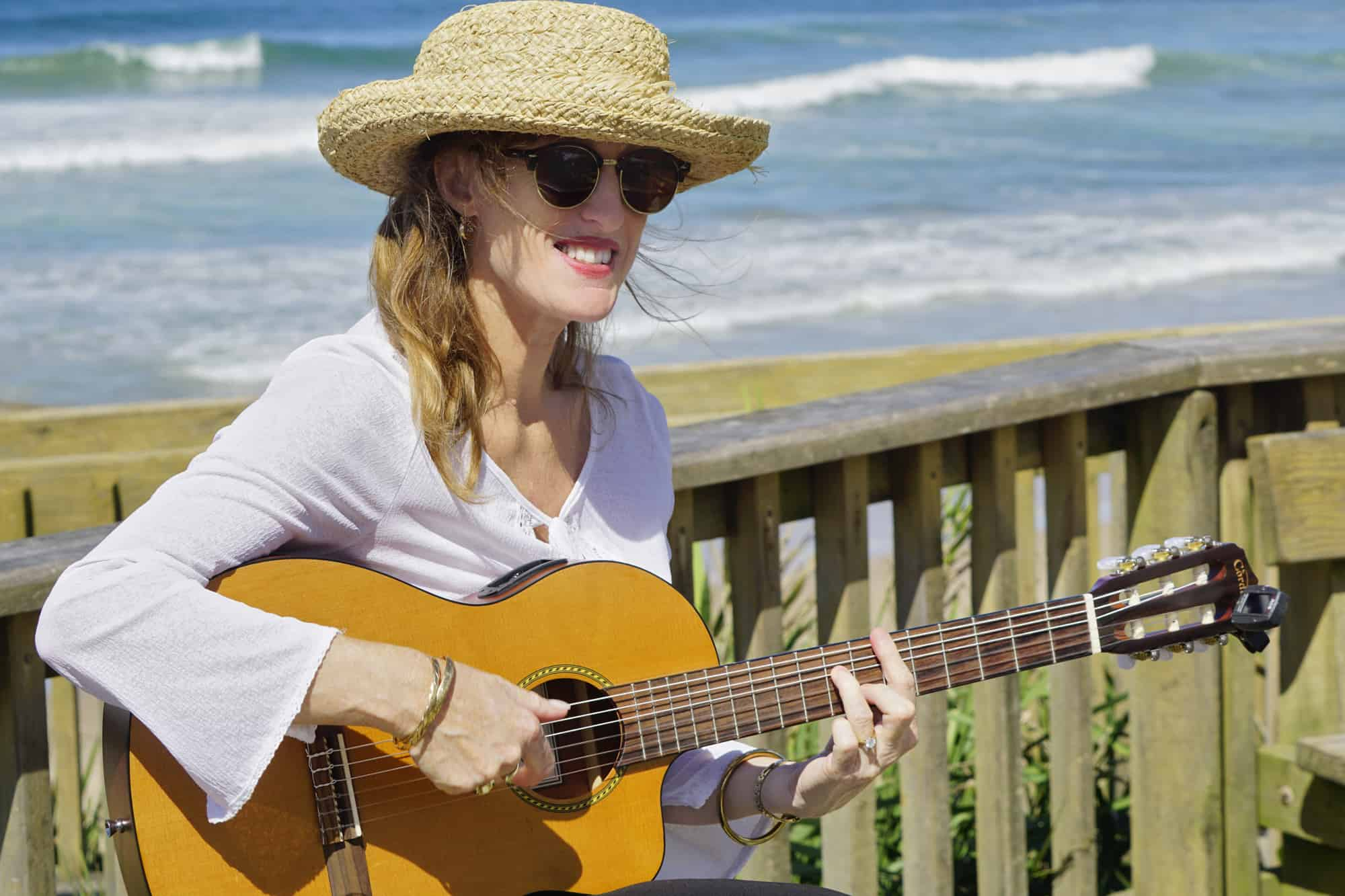 A woman in a straw hat playing classical guitar with the ocean behind her