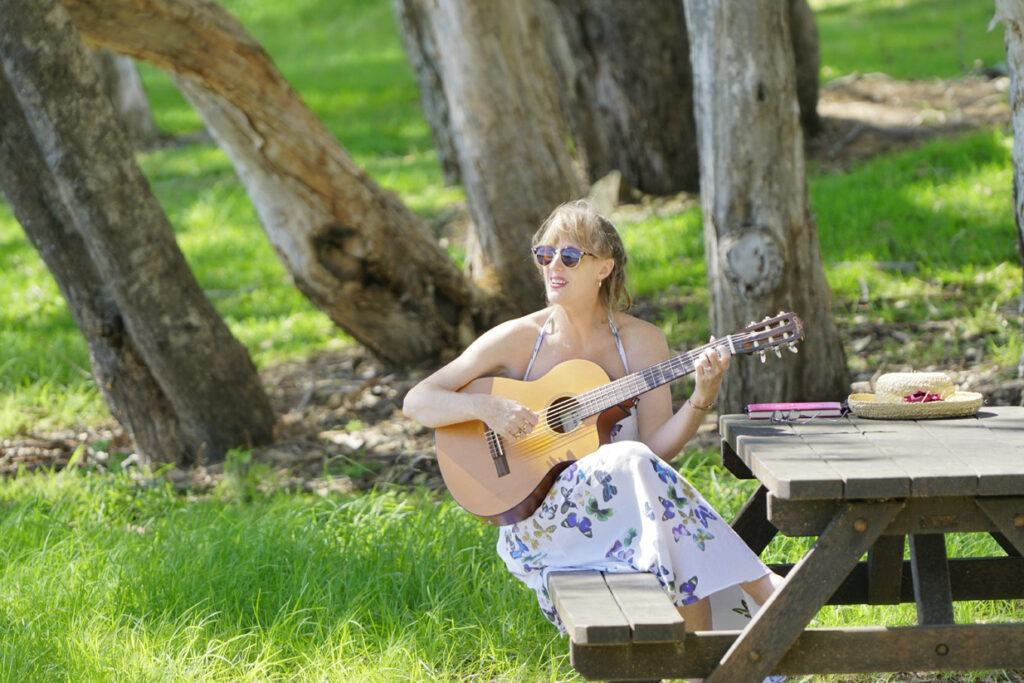 Lily singing and playing guitar in the park