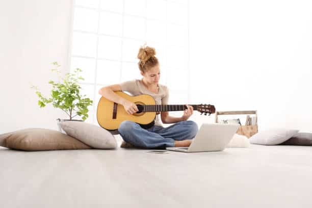 learn slowly, study. Young woman playing guitar with computer to watch