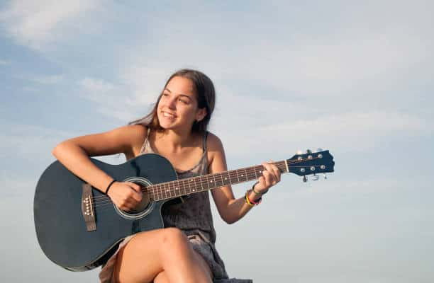 Young woman learning to play guitar