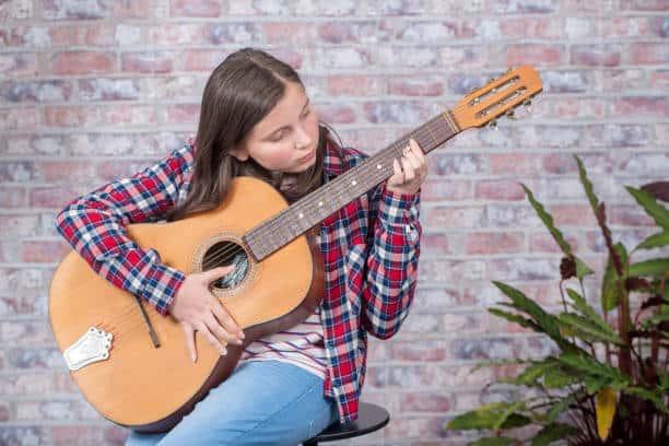 A young girl practising guitar