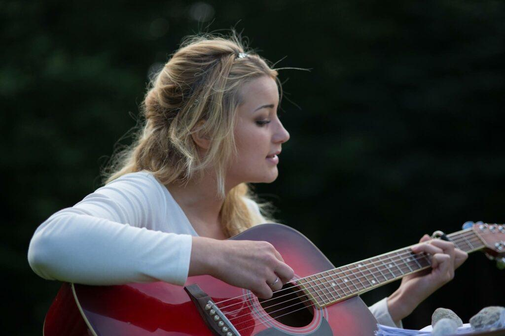 Young woman in white top playing red guitar