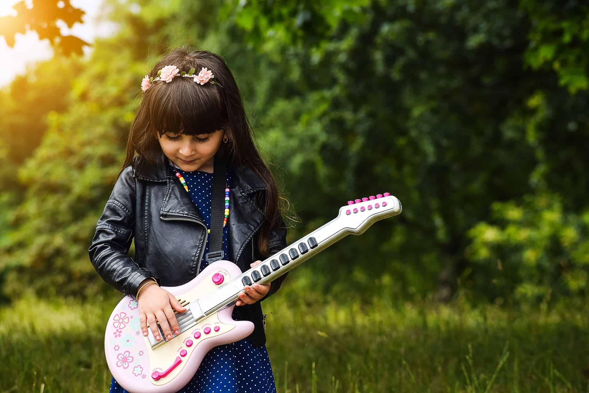 Small hands of a little girl playing pink guitar