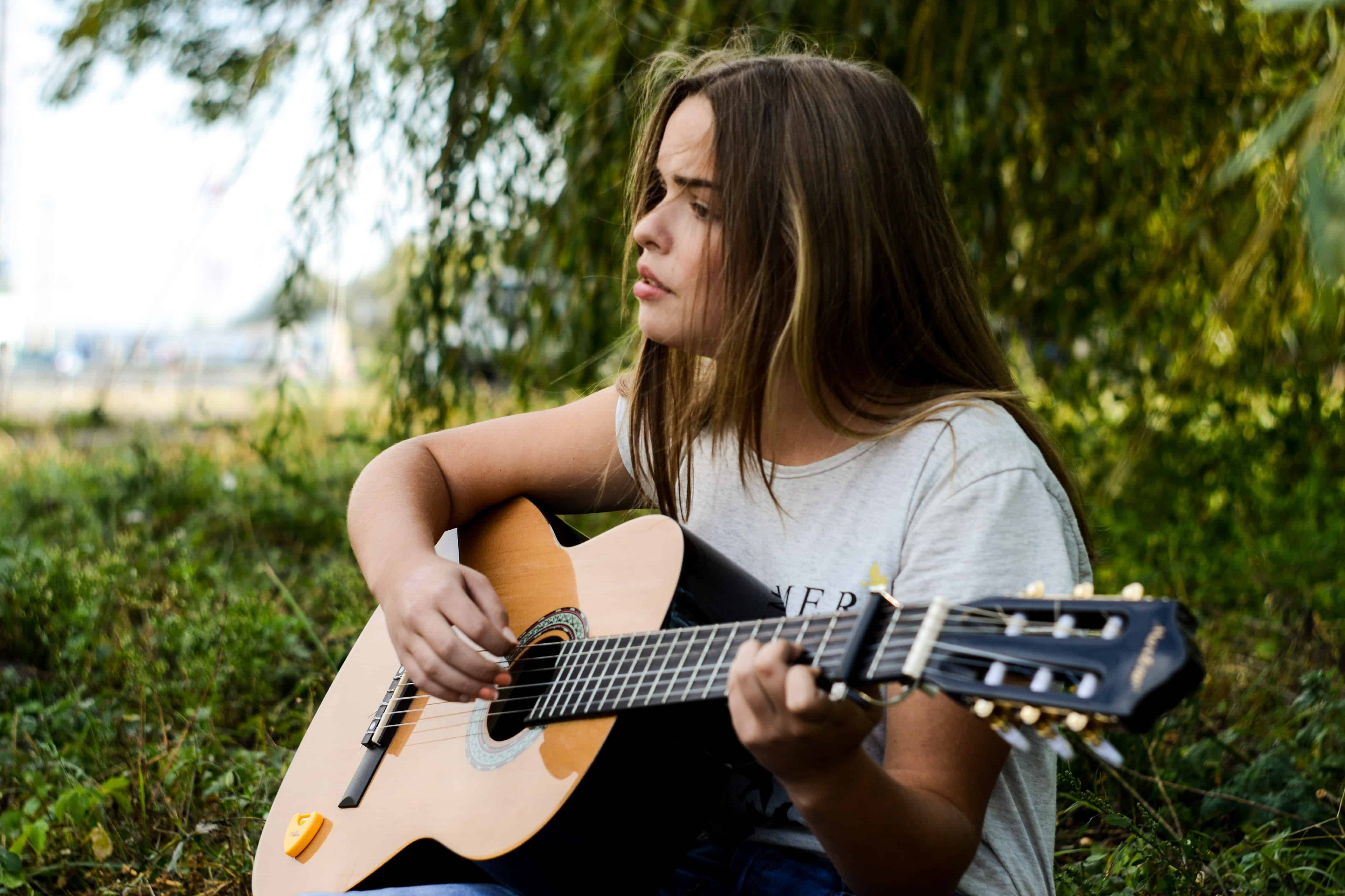 Girl playing guitar and challenge herself to learn to play