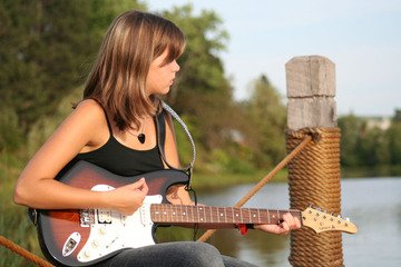 Young girl sitting on a pier with her electric guitar