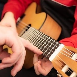 Small child with small guitar in lap with adult hand in picture